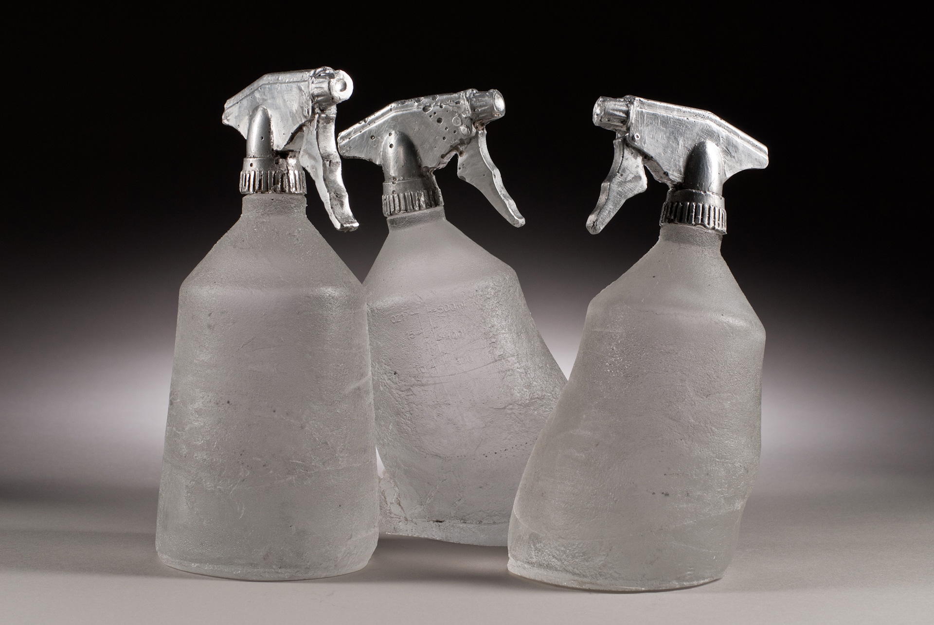 Three cast glass bottles , titled Spray Morped, with printed labels and cast aluminum sprayer nozzles.