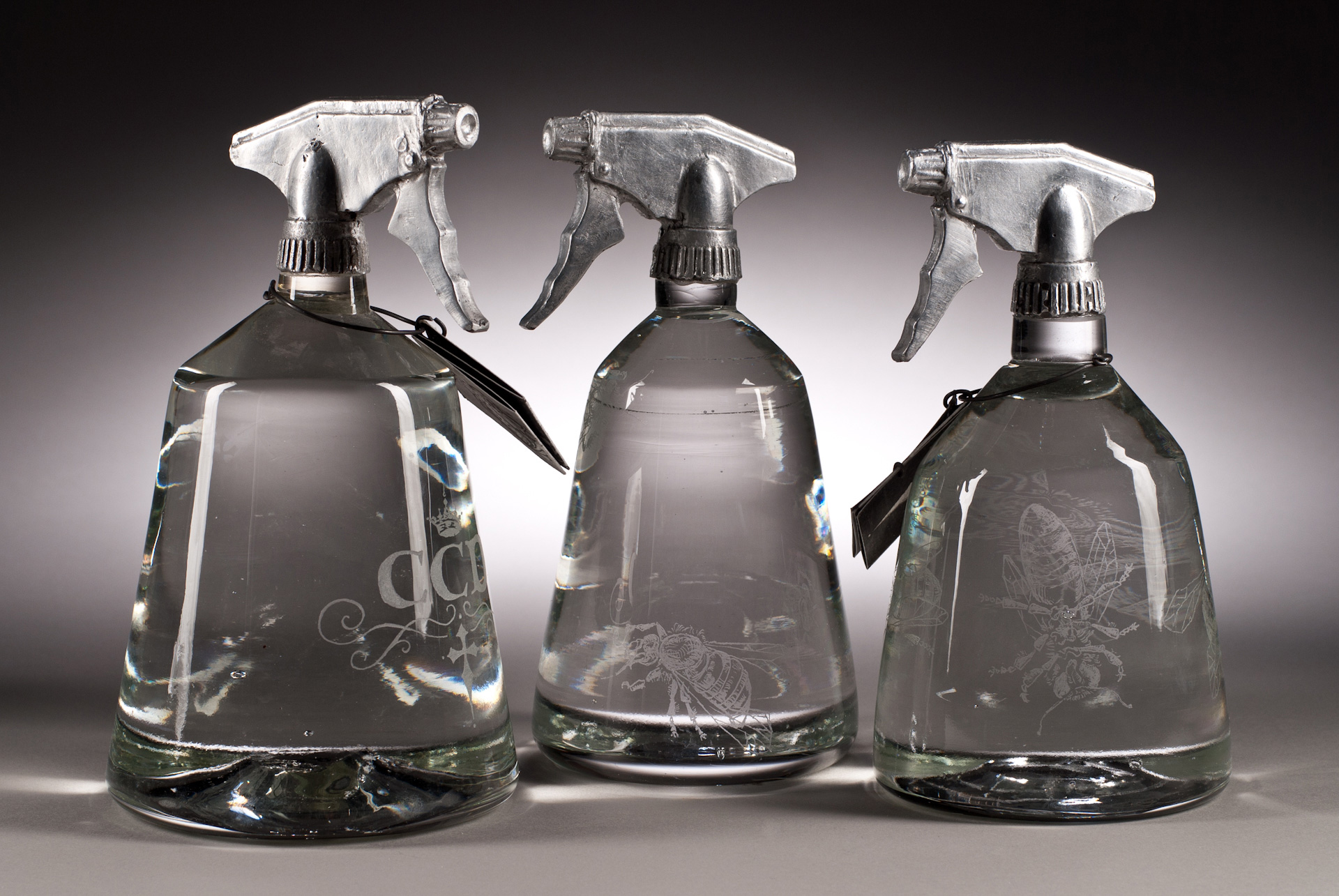 Three hand blown glass bottles , titled Spray, with printed labels and cast aluminum sprayer nozzles.
